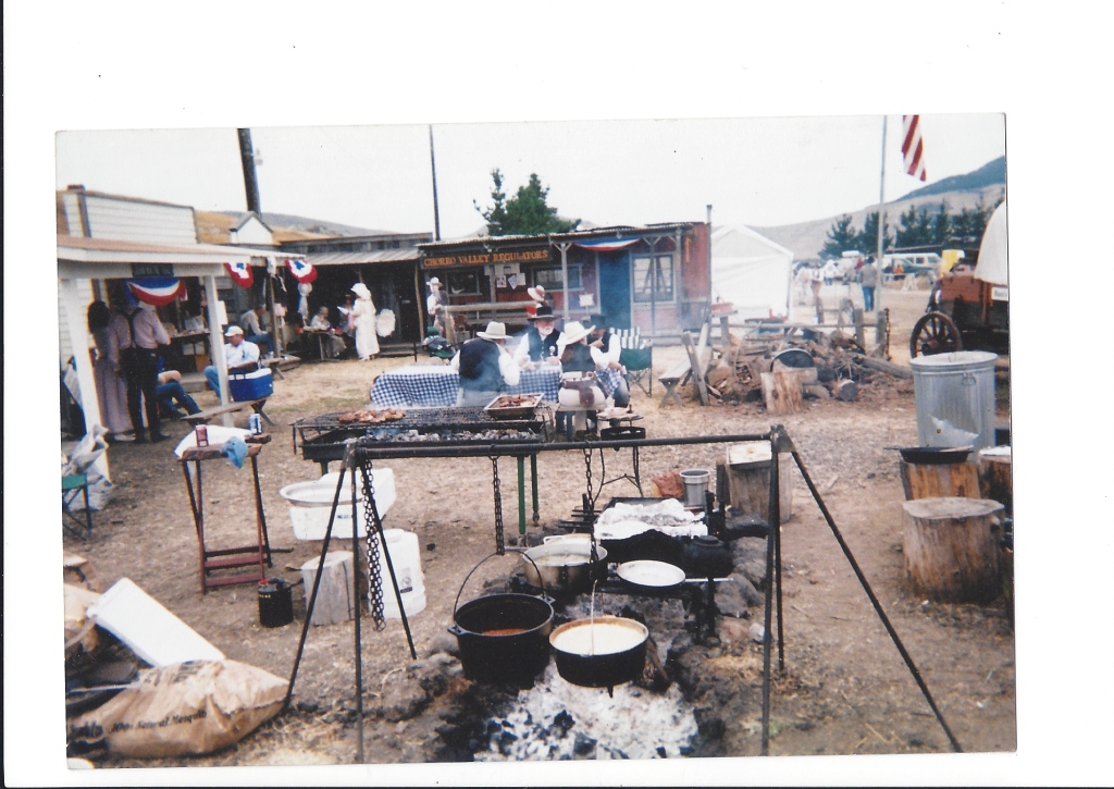18th century campfire cooking with cauldrons filled with bubbling goodness.  Hung off of tripods and other cooking methods.  People sitting around tables with blue checkered table clothes.   A true Cowboy cook out.
